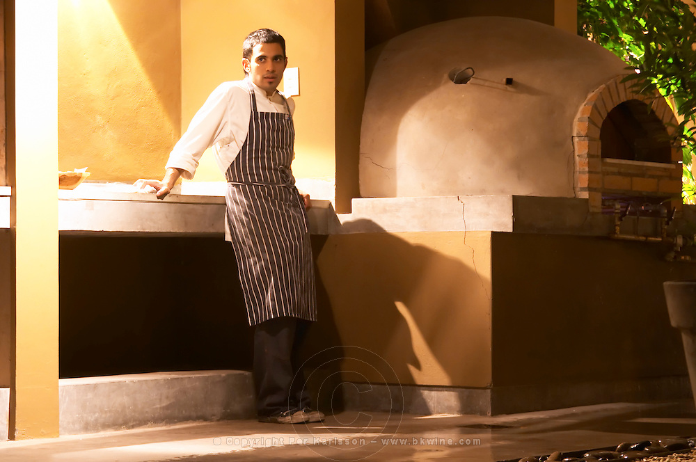 A cook waiting beside the special oven in the garden used to bake bread and other special things. The Dolly Irigoyen - famous chef and TV presenter - private restaurant, Buenos Aires Argentina, South America Espacio Dolli
