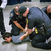 A demonstrator is taken into custody at Republican Presidential nominee Donald Trump during a rally in Asheville, NC.