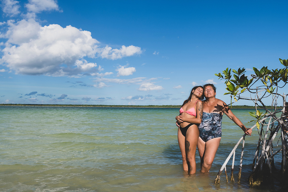 Bacalar, Mexico - June 2, 2021: Liliana, age 60, and her daughter Mailen, age 25, both from Argentina, pose for a portrait on a sunny afternoon at Bacalar Lagoon.