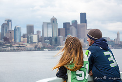 United States, Washington, Seattle. Passengers on a ferry approaching downtown Seattle, wearing shirts supporting the Seattle Seahawks football team.