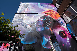 """© Licensed to London News Pictures; 02/04/2021; Bristol, UK. Artist Mr Cenz from London puts the finishing touches to """"United Souls United Goals"""", a giant mural of Jen Reid, the woman who stood on the plinth of the statue of Edward Colston after it was torn down at a Black Lives Matter protest in Bristol in 2020 and of whom a statue was made and temporarily placed on the plinth. The mural is on the wall by The Canteen on Stokes Croft directly opposite Banksy's Mild Mild West mural, and replaces an earlier mural of Breakdancing Jesus. The mural is launched by The Bristol Eighteen and has the welcoming message """"Rise up Bristol, stand tall... Bristol's a city for all"""" by poet Lawrence Hoo with Bristol's own street artist Inkie lending a hand to convey Lawrence Hoo's open-arms message of togetherness. The piece has been created to commemorate the Black Lives Matter protest in Bristol on June 7th 2020 and promote the ongoing global anti-racism movement. The Bristol Eighteen was formed, in the wake of the removal of Edward Colston's statue, to create a vehicle to raise funds for anti-racist educational organisations. Photo credit: Simon Chapman/LNP."""