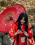 "Costumed Japanese woman with parasol and fan. Matsumoto Castle is a ""hirajiro"" - a castle built on plains rather than on a hill or mountain, in Matsumoto, Nagano Prefecture, Japan. Matsumotojo's main castle keep and its smaller, second donjon were built from 1592 to 1614, well-fortified as peace was not yet fully achieved at the time. In 1635, when military threats had ceased, a third, barely defended turret and another for moon viewing were added to the castle. Interesting features of the castle include steep wooden stairs, openings to drop stones onto invaders, openings for archers, as well as an observation deck at the top, sixth floor of the main keep with views over the Matsumoto city."