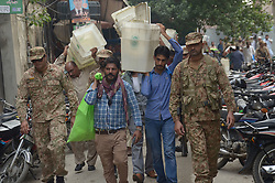July 26, 2018 - Lahore, Punjab, Pakistan - Polling officers with army soldiers carry the election material escorts them as they come out from a voting material distribution. The election Commission announced that the country's security forces will be deployed to polling stations to ensure free, fair and transparent national elections. (Credit Image: © Rana Sajid Hussain/Pacific Press via ZUMA Wire)
