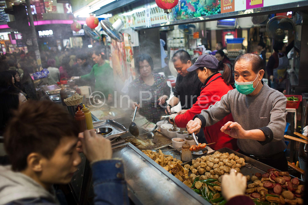 A food stall serves up delicious Chinese fast food to hungry Christmas shoppers and commuters on their way home from work in Times Square. The food is steaming hot and a mix of sea food on sticks, chicken or pork. The man serving wears a face mask to protect his many customers and himself from spreading diseases. 7 million people live on 1,104km square, making it Hong Kong the most vertical city in the world.