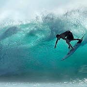 A surfer rides a wave at Desert Point, Lombok, Indonesia. This remote surf spot attracts some of the best surfers in the world.