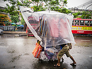 30 MAY 2013 - BANGKOK, THAILAND:   A man pushes a rack of clothes through the rain to Bobae Market in Bangkok. Bobae Market is a 30 year old famous for fashion wholesale and is now very popular with exporters from around the world. Bobae Tower is next to the market and  advertises itself as having 1,300 stalls under one roof and claims to be the largest garment wholesale center in Thailand.    PHOTO BY JACK KURTZ