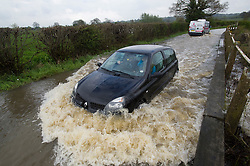 © London News Pictures. 29/04/2012. Margaretting, UK. A 4x4 car driving through flood water on a road near the town of Margaretting in Essex on April 29, 2012 . The nearby river Wid broke it's banks following torrential rainfall. Photo credit : Ben Cawthra /LNP
