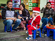 22 DECEMBER 2017 - HANOI, VIETNAM: A child in a Santa Claus suits sits with his family in a cafe before the Christmas show at St. Joseph's Cathedral in Hanoi. There are about 5.6 million Catholics in Vietnam. The Cathedral was one of the first structures built by the French during the colonial era and was opened in 1886. It's one of the most popular tourist attractions in Hanoi.    PHOTO BY JACK KURTZ