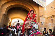 Parading on the back of a camel, a Rajasthani women in traditional bridal costume at the Desert Festival on 29th January 2018  in Jaisalmer, Rajasthan, India. It is an annual event that take place in February month in the beautiful city Jaisalmer. It is held in the Hindu month of Magh February, three days prior to the full moon.