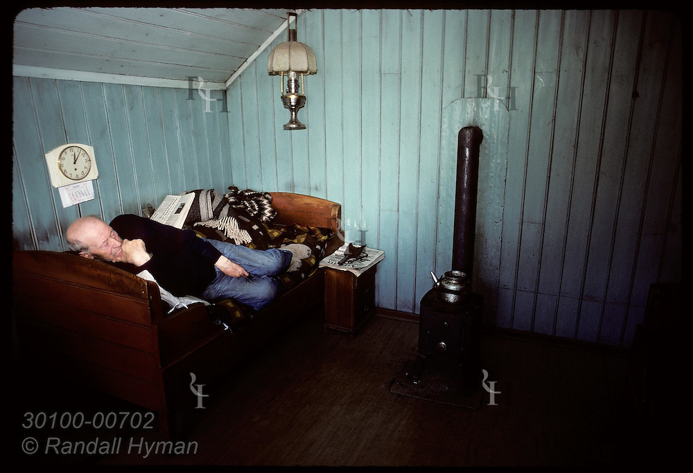 Sigurjón Jóhannsson curls up on bed beneath clock-and-calendar beside coal stove in his farmhouse at Kot beneath Hekla; Rangárvellir, Iceland