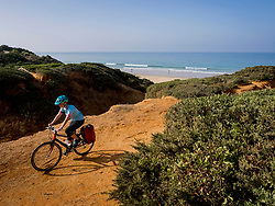 Mountain biker riding dirt track near beach and sea