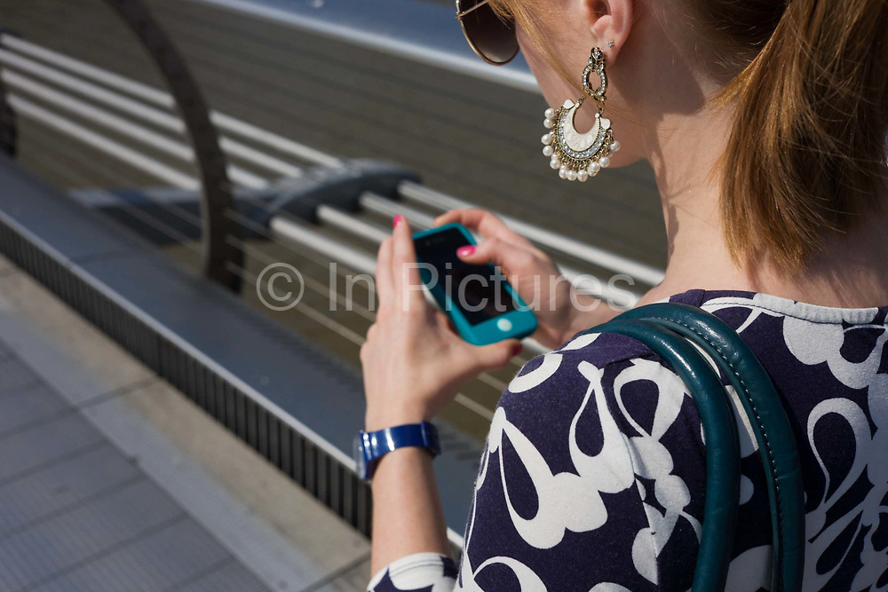 A young woman walks over London's Millennium Bridge while using her smartphone. Seen from over her left shoulder we look at her earrings that hang from her lobes and the traps of her shoulder bag. As she walks over the bridge her attention is the touch screen that shows her messages and she replies to the latest, looking down and thumbing the screen with pink painted nails.