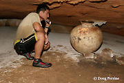guide for Ian Anderson's Caves Branch Tours examines ancient Mayan pottery in Footprints Cave or River Cave, Cayo District, Belize, Central America