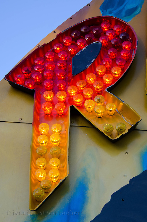 """The letter """"R"""" glows from a carnival marquee at dusk on a summer evening."""