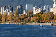 """The False Creek Ferry """"Spirit of False Creek"""" crosses False Creek from Sunset Beach to Granville Island.  Sunset Beach and apartment towers in the West End of Vancouver are in the background. Photographed from Granville Island in Vancouver, British Columbia, Canada."""