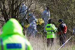 © licensed to London News Pictures. Leigh, Greater Manchester, UK  10/04/2012. Police guard the scene as forensic investigators search where the burned body of a man has been discovered. A tent has been erected in a wooded area near to Pennington Road, adjascent to a brook. Several police are at the scene. Photo credit should read Joel Goodman/LNP