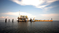 26 May 2010. Barataria Bay to Grand Isle, Jefferson/Lafourche Parish, Louisiana. <br /> A natural gas platform. The fragile grass lands perched at the mouth of mississippi delta is all that seperates land from the Gulf of Mexico. The region is strategically vital to the American oil and gas industry and a major player in America's seafood industry. BP's catastrophic oil spill continues to spew a black tide of death which continues to encroach upon everything in the region. The economic impact is devastating with shrimp boats tied up, vacation rentals and charter boat fishing trips are cancelled. The only real business is cleaning up big oil's disasterous screw up. Oil from the Deepwater Horizon catastrophe is evading booms laid out to stop it thanks in part to the dispersants which means the oil travels at every depth of the Gulf and washes ashore wherever the current carries it. <br /> Photo credit; Charlie Varley<br /> www.varleypix.com