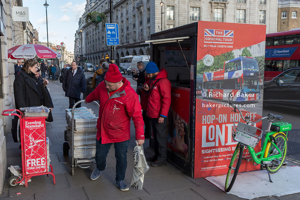 An Evening Standard vendor pulls a trolley with stacked copies of the latest edition of London newspapers,opposite the Ritz Hotel on Piccadilly in central London, on 11th February 2020, in London, England.
