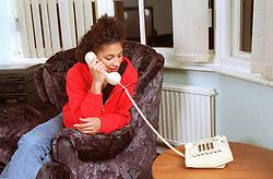 Teenage girl sitting in living room talking on telephone,
