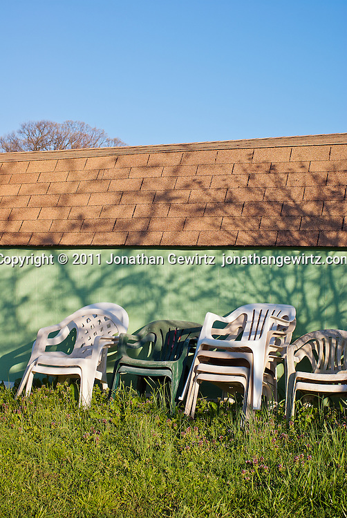 Rows of plastic lawn chairs stacked against the wall of a garden shed. WATERMARKS WILL NOT APPEAR ON PRINTS OR LICENSED IMAGES.