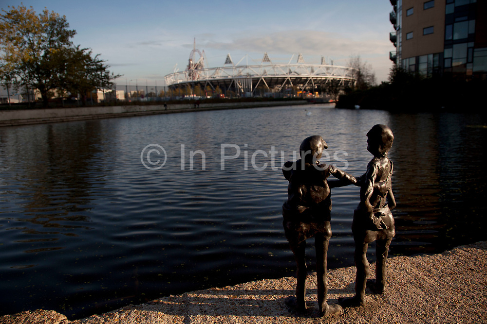 Small scale sculptures look out over the Lea Navigational Canal towards the 2012 Olympic Stadium at Hackney Wick, East London, UK.