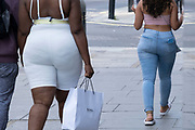 A woman wearing tight white clothing is reflected in shop windows as she walks along Oxford Street on 13th August 2020 in London, United Kingdom. This area is the main shopping district in the capital.