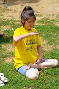 Asian American woman age 30 practicing meditation in the lotus position. Dragon Festival Lake Phalen Park St Paul Minnesota USA