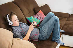 Boy with headphones and smartphone on couch