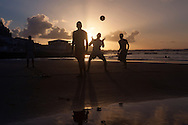 BAHIA FORMOSA, BRAZIL: Young people playing football at sunset on the beach at Bahia Formosa, Brazil.