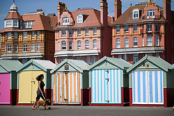 © Licensed to London News Pictures. 03/07/2018. Hove, UK. A woman walks her dog past colourful beach huts on the seafront at Hove, East Sussex on the south coast of England, as a heatwave continues across the UK. Photo credit: Ben Cawthra/LNP