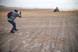 AREQUIPA, Jan. 11, 2019  A man takes photos as he stands beside the words ''DAKAR 2019'' written by himself during the 4th stage of the 2019 Dakar Rally Race, near La Joya, Arequipa province, Peru, on Jan. 10, 2019. (Credit Image: © Xinhua via ZUMA Wire)