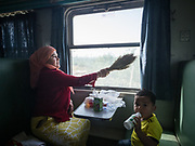 A Uighur woman cleans the window off the sand with a broom provided by the controler. Life inside the train - mostly Muslim Uighur people  ride this train.