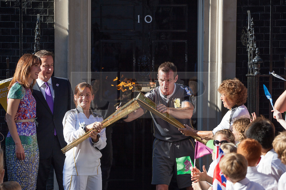 © licensed to London News Pictures. London, UK 26/07/2012. Kate Nesbitt passes the torch to Florence Rowe in Downing Street. Photo credit: Tolga Akmen/LNP
