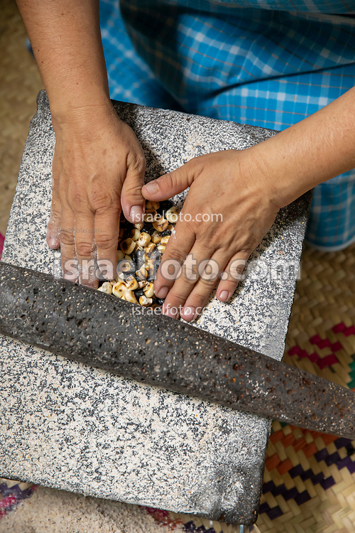 Toasted corn and black beans being grinded in a metate or stone hand mill. / Maíz y frijol tostado siendo molidos en un metate
