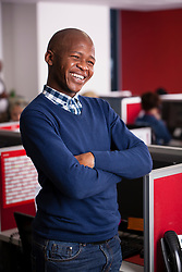 CAPE TOWN, SOUTH AFRICA, MAY 24, 2017. A laughing young black Xhosa African man stands in front of his red office cubicle wearing a deep blue cardigan and black jeans.(Picture: JULIAN GOLDSWAIN)