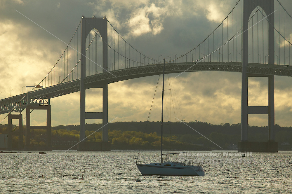 Newport, RI 2006 - Newport bridge with dramatic light in clouds and single moored yacht centered under it.