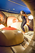 A woman bounces in Jump for Joy, a bouncy castle of breasts in the Museum of Sex.