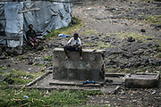 A boy sits on a broken water stand in the outskirt of Goma.