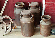 Old brown metal milk canisters. Bridgeton Historic District, Indiana: Bridgeton Covered Bridge (245 feet long) was rebuilt in historically accurate Burr Arch style in 2006 over Big Raccoon Creek (replacing 1868 bridge burnt by arson in 2005) on Bridgeton Road, Parke County, Indiana, USA. Bridgeton Mill was established 1823, rebuilt 1870, and is the oldest continuously operating mill west of the Allegheny Mountains. The mill grinds wheat into flour and corn into meal with 200 year-old French Buhr stones.