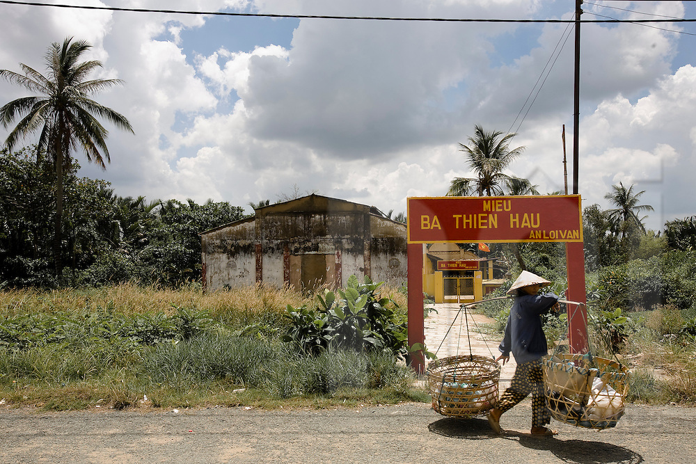 A Vietnamese woman wearing a conical hat and carrying a yoke passes a temple in District 2, Ho Chi Minh City, Vietnam, Southeast Asia, May 2011.