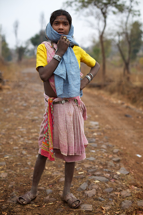 Adivasi (tribal) girl Atri Bai, 12, from the Baiga commumity in outside home village of Indripani. Atri Bai's family were relocated in 2002 from Bodhi Daldali to make way for the 668 hectare bauxite mine, run by Balco & Vedanta (Vedanta is a UK headquartered company). Families received Rs.100,000 per acre of lost land. As many survived by cultivating forest land, this amount did not properly compensate them for their loss. The Bodhi Daldali mine directly employs just 70 people. 750 contractors, most of them casual day-wage workers, provide the labour without which the mine would not function. <br /> <br /> Photo: Tom Pietrasik<br /> Kawardha District, Chhattisgarh. India<br /> February 20th 2011