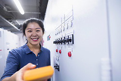 Young female engineer examining control panel with multimeter in an industrial plant, Freiburg im Breisgau, Baden-Wuerttemberg, Germany