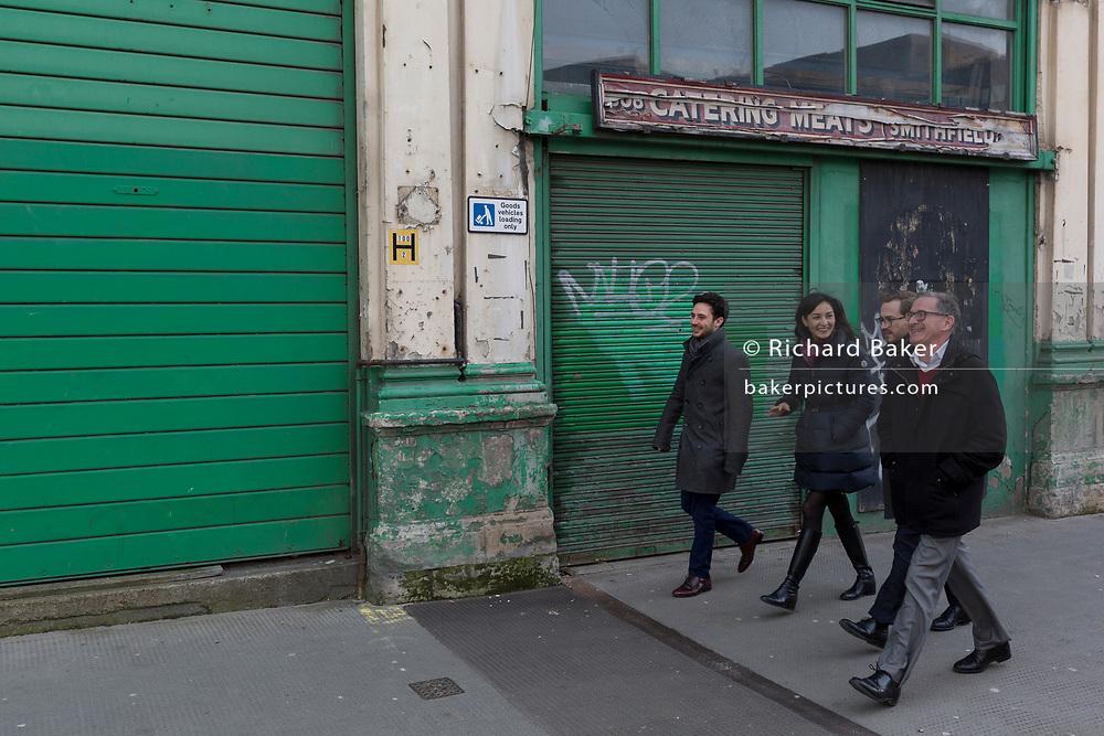 Lunchtime Londoners pass a closed butcher business in the former Smithfield meat market that is awaiting future redevelopment, on 20th November 2019, at Smithfield in the City of London, England. In March 2015, the Museum of London revealed plans to vacate its Barbican site and move into the General Market Building. The cost of the move is estimated to be in the region of £70 million and, if funding can be achieved, would be complete by 2021. There has been a market on this location since the Bartholomew Fair was established in 1133 by Augustinian friars.