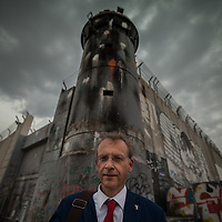 Owe Boersma of EAPPI in front of a tower on the separation wall in Bethlehem. The Israeli West Bank barrier or wall is a separation barrier in the West Bank. Israel calls it a security barrier while Palestinians and many others call it a racial segregation or apartheid wall. At a total length of 708 kilometres (440 miles) upon completion, the border traced by the barrier is more than double the length of the Green Line, with 15% running along it or in Israel, while the remaining 85% cuts at times 18 kilometres (11 miles) deep into the West Bank, isolating about 9.4% of it, leaving an estimated 25,000 Palestinians isolated from the bulk of that territory.