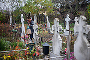 A woman visiting a grave on the local cemetary in Marginenii de Jos
