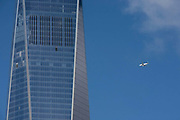 A jet aircraft flies past the newly-completed One World Trade Center (WTC) on what was Ground Zero on the September 11th 2001 attacks on New York City, USA. As an ironic coincidence, we see the airliner flying high over Manhattan, passing the tall skyscraper that is being finished. The 104-story supertall structure, which shares a name with the northern Twin Tower in the original World Trade Center that was destroyed in the September 11 attacks, stands on the northwest corner of the 16-acre (6.5 ha) World Trade Center site, on the site of the original 6 World Trade Center. It was architect Daniel Libeskind who won the 2002 competition to develop a master plan for the World Trade Center's redevelopment.
