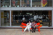 As if sagging because of their combined weight, two ladies sit on a curved bench, an artwork outside the Royal Festival Hall, on 120th July 2017, in London, England.