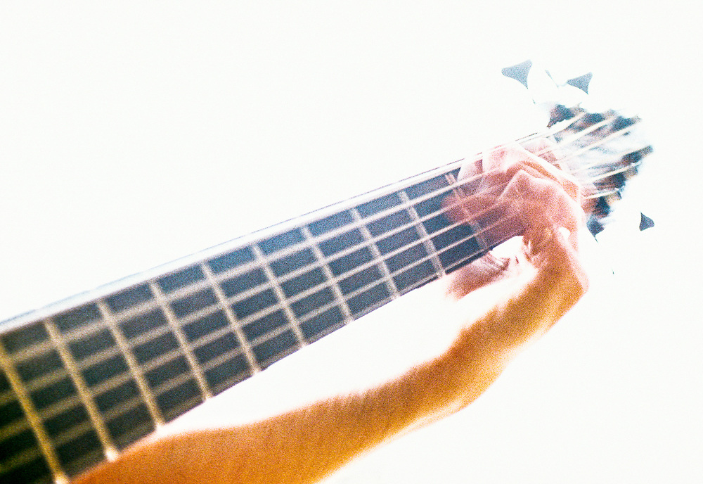 A mans left hand on the neck of a bass guitar while playing.
