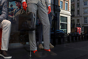 With a further 154 covid deaths reported in the last 24hrs, bringing the total to 43,081 in the UK during the Coronavirus pandemic, the red head and and hands of a menswear mannequin stands with others in the window of Suitsupply on Sackville Street where two red phone kiosks are located at the end of the street, on 24th June 2020, in London, England. Suitsupply is a men's fashion brand founded in 2000 by Fokke de Jong in Amsterdam.