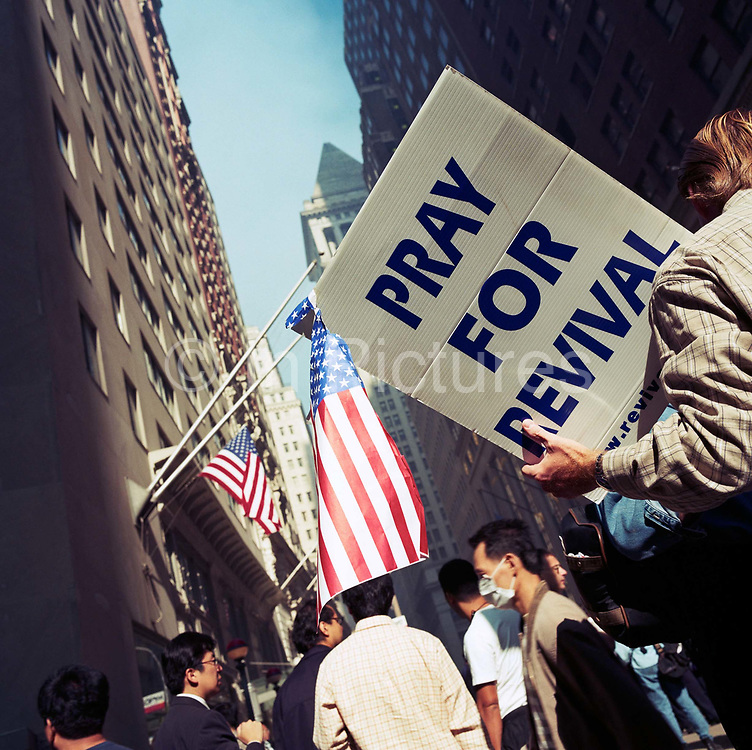 During a journey into America's hinterlands, days after the September 11th attacks in New York and Washington DC, crowds of New Yorkers gathered at barriers where streets were closed, near Ground Zero, to offer help for volunteers: Spare beds offered, free food distributed, and  offers of salvation. A man here has a board urging prayer and revival for those feeling spiritually adrift. American flags hang from buildings and businessmen and tourists talk in the street with some wearing dust masks. In outpourings of grief, anger and patriotic rhetoric, flags were flown as never before as America sought to express their emotions and a unity.